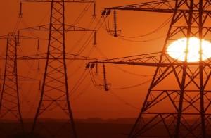 Setting Sun seen through a row of electricity pylons